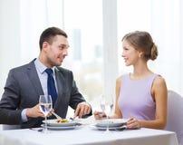 Uśmiechnięte pary łasowania zakąski przy restauracją Obraz Stock