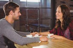 Uśmiechnięte pary mienia ręki i mieć kawa wpólnie Zdjęcie Royalty Free