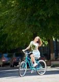 Uśmiechnięte piękne kobiety mienia peonie i jazda bicyklu błękitnego puszka pusta brukująca ulica z zielonymi drzewami wokoło obraz royalty free