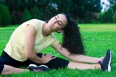 Uśmiechnięte sportsmenki rozciągania nogi na trawie Obraz Royalty Free