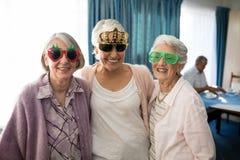 Uśmiechnięte starsze kobiety jest ubranym odkrywczość szkła fotografia stock