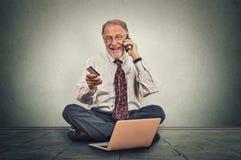 Uśmiechnięte starsze osoby obsługują robić rozkazowi na podłoga jego biuro telefonu komórkowego obsiadaniem Obraz Stock