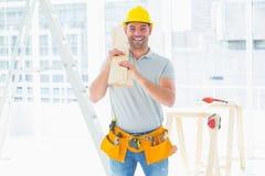Uśmiechnięte złotej rączki przewożenia deski w budynku Fotografia Royalty Free