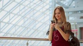 Uśmiechniętego żeńskiego blogger słuchające ulubione piosenki w hełmofonach podczas gdy pozujący dla selfie na smartphone kamerze zbiory wideo