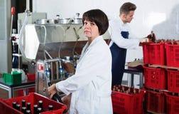 Uśmiechniętego żeńskiego pracownika rozlewniczy iskrzasty wino z maszyną Zdjęcia Stock
