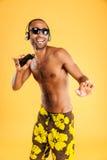 Uśmiechniętego afro amerykańskiego mężczyzna słuchająca muzyka w hełmofonach Fotografia Stock