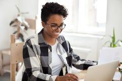 Uśmiechniętego amerykanin afrykańskiego pochodzenia żeńska praca z laptopem i papierami zdjęcie stock
