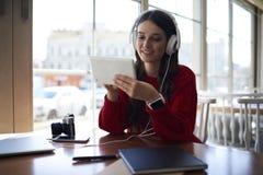 Uśmiechniętego atrakcyjnego żeńskiego ucznia miłośnika muzyki słuchający ulubeni składy zdjęcia royalty free
