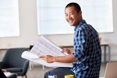 Uśmiechniętego Azjatyckiego architekta czytelniczy projekty w biurze Zdjęcie Royalty Free