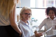 Uśmiechniętego dojrzałego bizneswomanu mienia biznesowa odprawa z pracownikami obraz stock