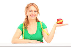 Uśmiechniętego dojrzałego kobiety mienia czerwony jabłko i pomiarowa taśma zdjęcia royalty free