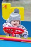 Uśmiechniętego dziecka napędowy samochód na boisku Zdjęcie Royalty Free