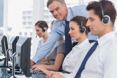 Uśmiechniętego kierownika centrum telefonicznego pomaga pracownik obraz royalty free
