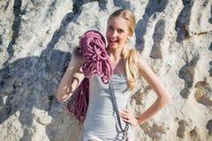 Uśmiechniętego kobiety mienia wspinaczkowy wyposażenie opiera przy skałą Obraz Royalty Free