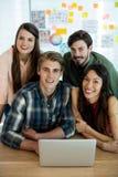 Uśmiechniętego kreatywnie biznesu drużynowy dyskutować nad laptopem obraz stock