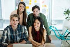 Uśmiechniętego kreatywnie biznesu drużynowy dyskutować nad laptopem fotografia royalty free