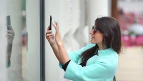 Uśmiechniętego kupującego żeńska bierze fotografia szklanej gabloty wystawowej mody smartphone sklepowy używa środek w górę zdjęcie wideo