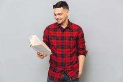 Uśmiechniętego mężczyzna czytelnicza książka w studiu Zdjęcia Stock