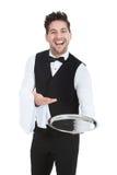 Uśmiechniętego młodego kelnera mienia porci pusta taca zdjęcie stock