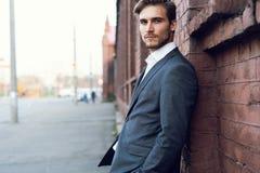 Uśmiechniętego młodego męskiego kierownika formalny ubieram opierać na ścianie outdoors zdjęcie royalty free