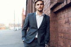Uśmiechniętego młodego męskiego kierownika formalny ubieram opierać na ścianie outdoors obrazy royalty free