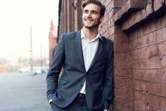 Uśmiechniętego młodego męskiego kierownika formalny ubieram opierać na ścianie outdoors zdjęcia royalty free