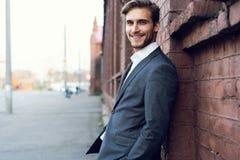 Uśmiechniętego młodego męskiego kierownika formalny ubieram opierać na ścianie outdoors fotografia royalty free