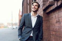 Uśmiechniętego młodego męskiego kierownika formalny ubieram opierać na ścianie outdoors zdjęcia stock