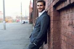 Uśmiechniętego młodego męskiego kierownika formalny ubieram opierać na ścianie outdoors zdjęcie stock