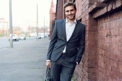 Uśmiechniętego młodego męskiego kierownika formalny ubieram opierać na ścianie outdoors obraz stock