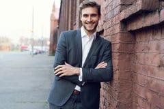 Uśmiechniętego młodego męskiego kierownika formalny ubieram opierać na ścianie outdoors obrazy stock
