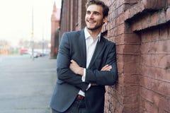 Uśmiechniętego młodego męskiego kierownika formalny ubieram opierać na ścianie outdoors obraz royalty free