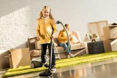 uśmiechniętego małego dziecka czyści pokój z próżniowy czystym podczas gdy macierzysta czytelnicza książka na kanapie zdjęcie royalty free
