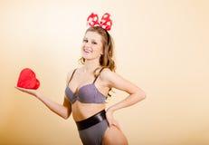 Uśmiechniętego pinup dziewczyny mienia czerwony serce nad śmietanką Obrazy Royalty Free