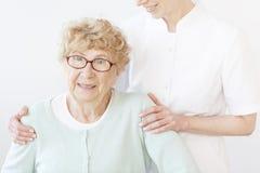 Uśmiechniętego pomocniczego przytulenia stara dama Obraz Royalty Free