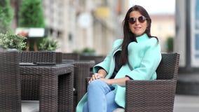 Uśmiechniętego splendoru żeński relaksujący obsiadanie na krześle przy plenerową cukiernianą cieszy się przerwą przy miasta tłem zbiory wideo