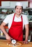 Uśmiechniętego szefa kuchni tnąca pizza z krajaczem Fotografia Stock