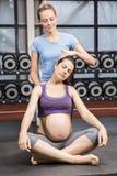 Uśmiechniętego trenera pomaga kobieta w ciąży rozciąga jej szyję obraz royalty free