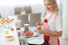 Uśmiechniętej blondynki kobiety kulinarne babeczki w kuchni Obraz Royalty Free