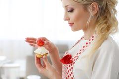 Uśmiechniętej blondynki kobiety kulinarne babeczki w kuchni Obrazy Stock