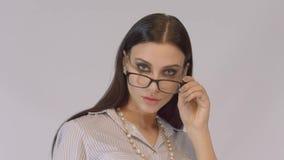 Uśmiechniętej brunetki biznesowa kobieta jest ubranym białych szkła i koszula zdjęcie wideo