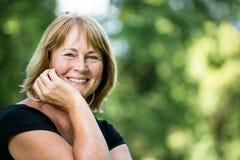 Uśmiechniętej dojrzałej kobiety plenerowy portret fotografia royalty free