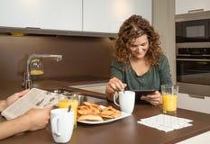 Uśmiechniętej dziewczyny czytelnicza wiadomość w pastylce przy śniadaniem zdjęcie stock