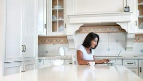Uśmiechniętej freelancer kobiety writing pracujący tekst używać laptop przy rocznika domu kuchnią zdjęcie wideo