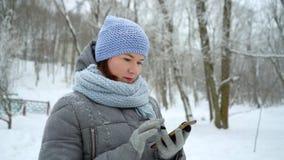 Uśmiechniętej kobiety czytelnicze wiadomości na telefonie w zima parku zbiory