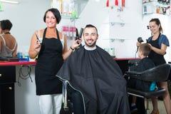 Uśmiechniętej kobiety fachowy fryzjer z nożycami zdjęcie royalty free