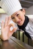 Uśmiechniętej kobiety kucbarski gestykuluje ok podpisuje wewnątrz kuchnię Zdjęcia Royalty Free