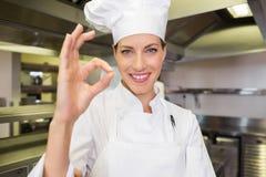 Uśmiechniętej kobiety kucbarski gestykuluje ok podpisuje wewnątrz kuchnię Fotografia Royalty Free