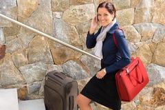 Uśmiechniętej kobiety telefonu opowiada biznesowy podróżny gnanie Obrazy Royalty Free