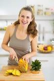 Uśmiechniętej młodej kobiety tnący ananas obraz stock